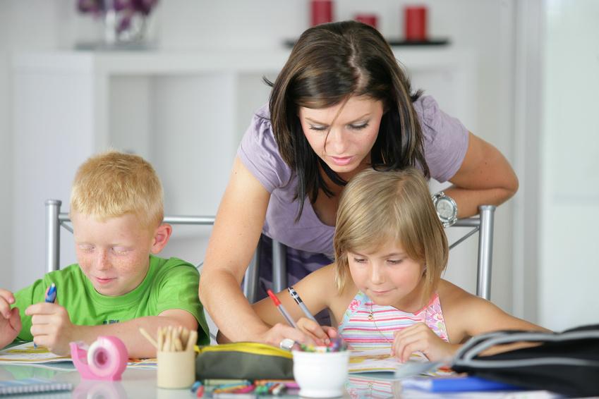 femme aidant un garçon et une fille à faire leurs devoirs